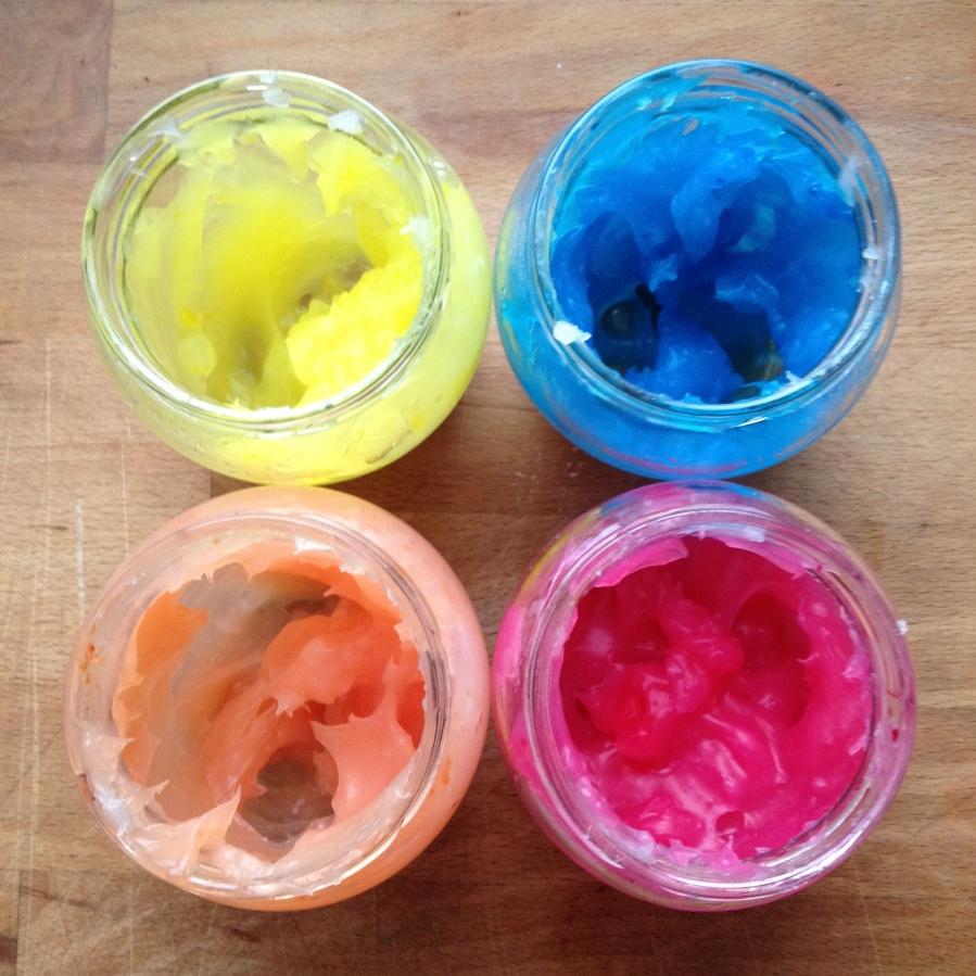 4 tarros con pintura comestible de color rosa, naranja, amarillo y azul